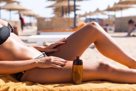 suncare: Sensuous slim woman applying suntan oil