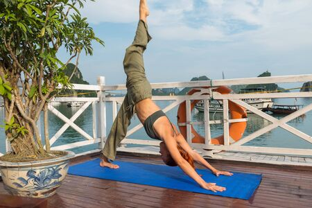 Young woman practicing yoga on the upper deck of ship. Morning time just after sunrise