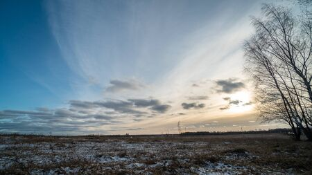 Beautiful blue sky and clouds with setting sun over frozen field in Russian countryside