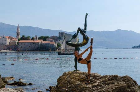 Tourist posing for a photo near statue