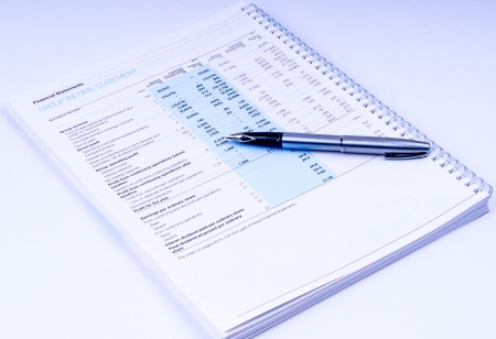 financial statements with pen on white background photo