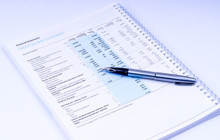 group income statement with pen on white background photo