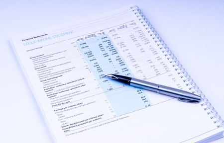Income statement with pen on white background photo