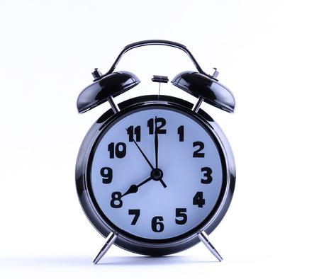 12 o'clock: Alarm clock on white with  eight o Stock Photo