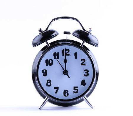 12 o'clock: Alarm clock on white with  twelve o