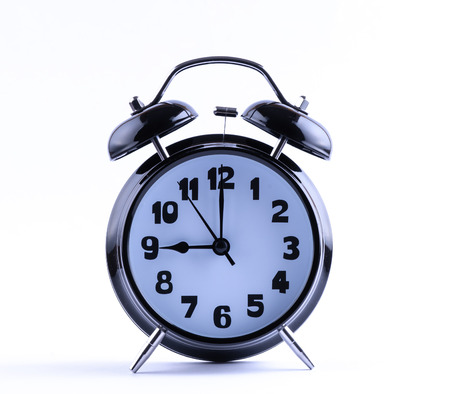 12 o'clock: Alarm clock on white with  nine o