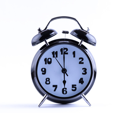 12 o'clock: Alarm clock on white with  six o