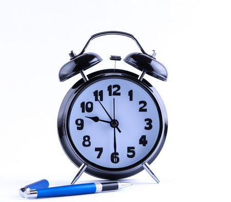 Alarm clock on white with  pen closeup photo