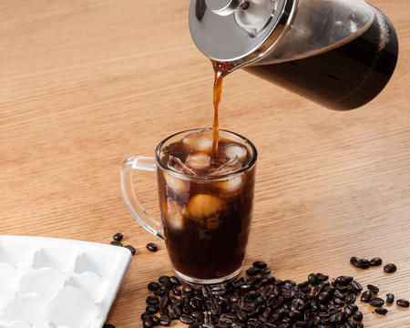 americano: Pouring coffee over ice to make a full glass of iced coffee. Stock Photo