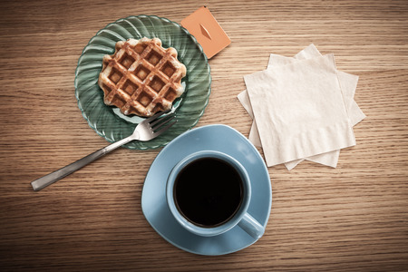 serwetki: Napkins next to coffee and a snack.
