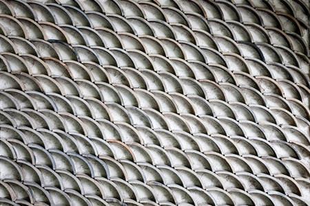A somewhat grungy fish scales like pattern on a wall.
