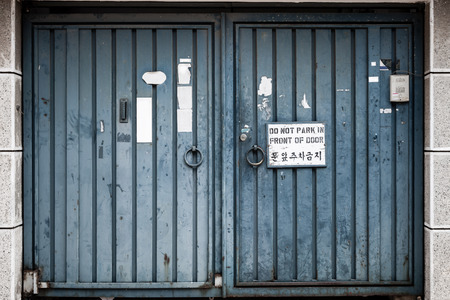 abused: Very weathered and abused metal blue double doors with a sign, Do Not Park In Front Of Door, and Hangul (Korean) translation.
