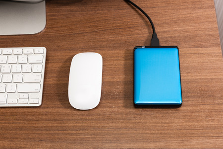 An external hard drive sitting on a desk top next to a computer, used for extra storage for extraneous data.