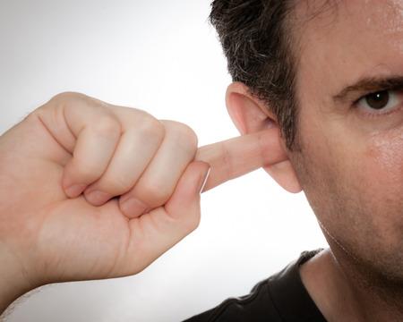 oreja: Un hombre está usando un dedo para limpiar sus oídos.