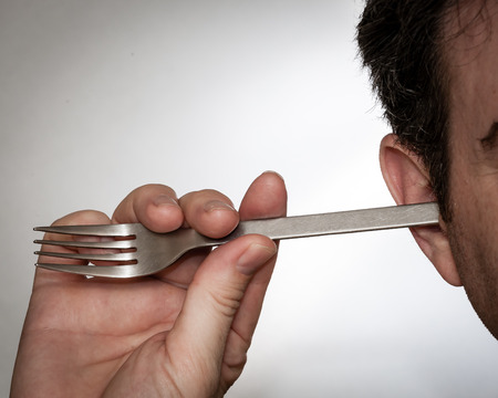 A man is using a fork to clean out his ears. Stock Photo