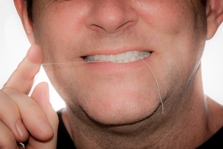 flossing: A man is practicing good dental hygiene by flossing.