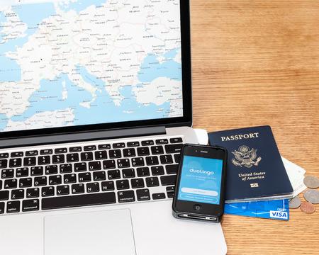 tarjeta visa: Se�l, Corea del Sur - 29 de julio 2015; Un editorial ilustrativo de la planificaci�n de viajes utilizando un mapa de aplicaci�n en un ordenador port�til, la aplicaci�n de aprendizaje de idiomas Duolingo en un iPhone, pasaporte, tarjeta de d�bito Visa, y algo de dinero y monedas extranjeras. Editorial
