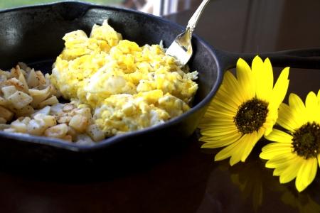 papas doradas: Hierro sartén pequeña con huevos revueltos y croquetas de patata