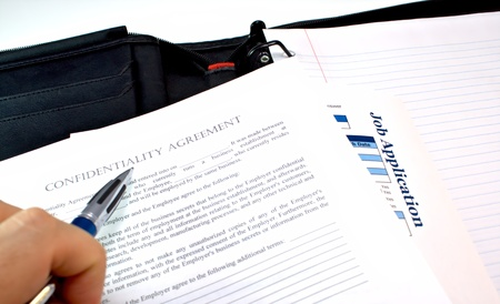 clause: Male hand looking at confidentiality agreement and job application