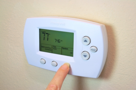 air conditioning: Female hand setting a digital thermostat
