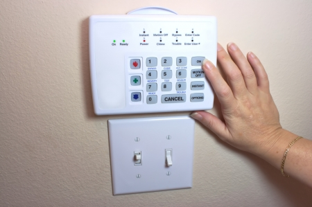 Female arming home security system photo