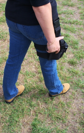 holster: Female wearing leg holster with hand on pistol prepared to draw and fire
