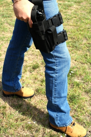 holster: Female with leg holster and hand on pistol Stock Photo