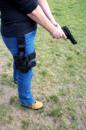 holster: Female with pistol drawn ready to take aim and fire Stock Photo