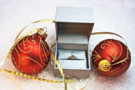 Engagement ring in silver box with two red and gold christmas ornaments with snow background Stock Photo