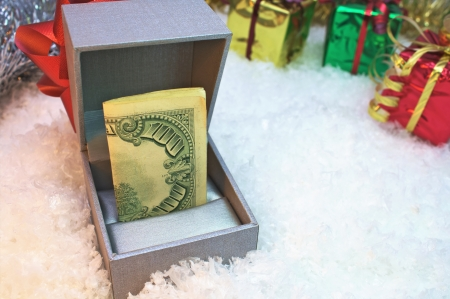 A one hundred dollar bill in a silver gift box Stock Photo