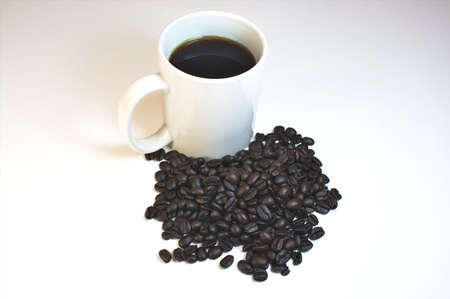 Cup of coffee with whole coffe beans isolated on white