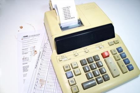 manchas de cafe: Los formularios de impuestos con manchas de caf� y cinta de la m�quina sumadora con nuevos impuestos Foto de archivo