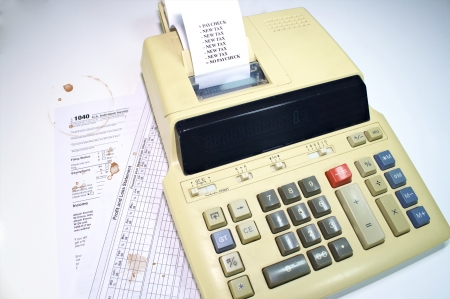 Tax forms with coffee stains and adding machine tape with new taxes Stock Photo