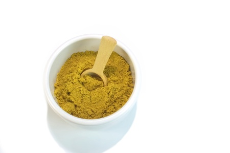 Curry powder in small container with wooden spoon for cooking