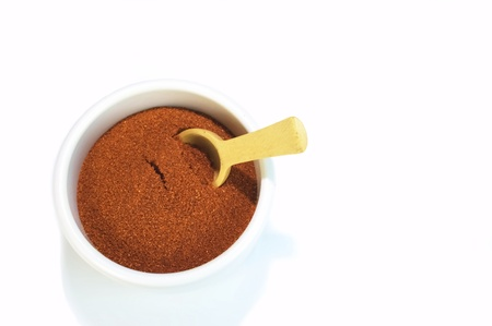 Small container of paprika with wooden spoon for cooking
