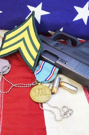 Pistol with military medal, dog tags, and patch