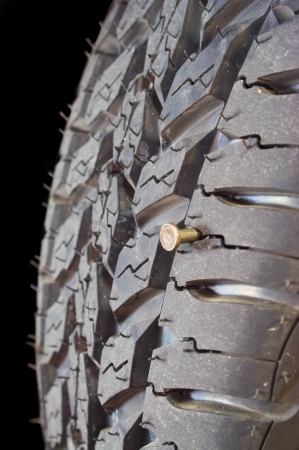 Close up of new tire with a screw in it