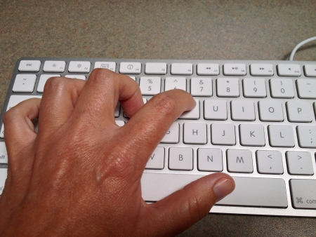 Left hand typing on an Apple keyboard Banco de Imagens