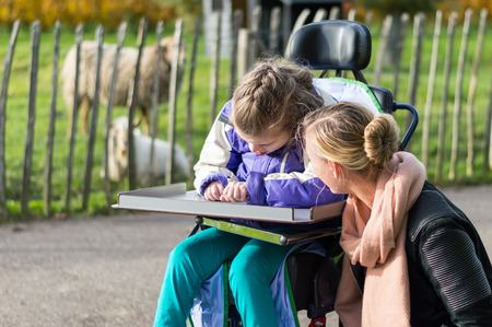 personas sentadas: Chica minusválidos en silla de ruedas al aire libre con asistente de cuidado Foto de archivo