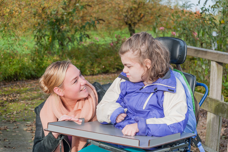 Disabled girl in a wheelchair together with a care assistant