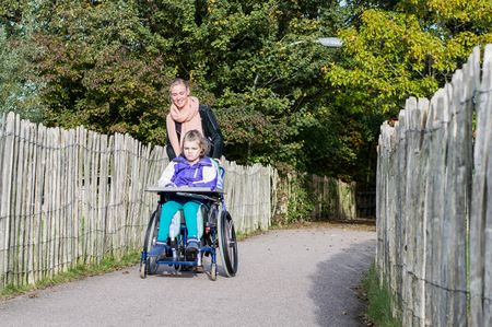 Disabled girl in a wheelchair outside together with a care assistant
