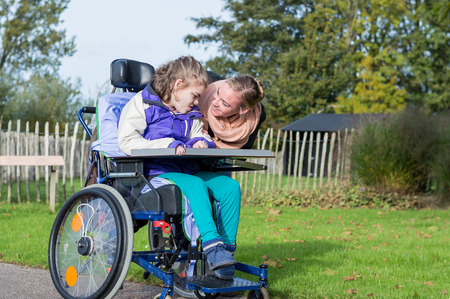 Disabled girl in a wheelchair outside with a care assistant