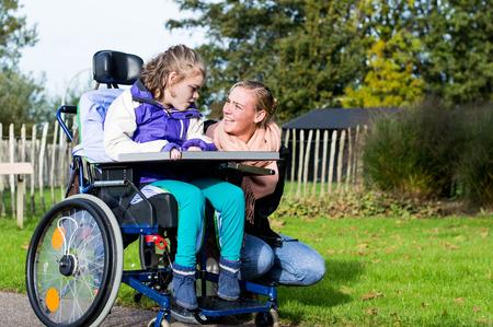 silla de ruedas: Un niño con discapacidad en una silla de ruedas con asistente de cuidado