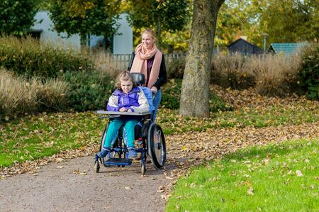 Un niño con discapacidad en una silla de ruedas con asistente de cuidado Foto de archivo - 47991011