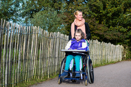 health care provider: Disabled child and a wheelchair with care assistant Stock Photo
