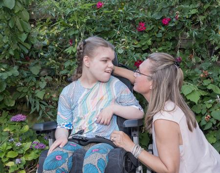 Handicap een gehandicapte meid in een rolstoel ontspannen samen met een vrijwillige zorgverlener Stockfoto