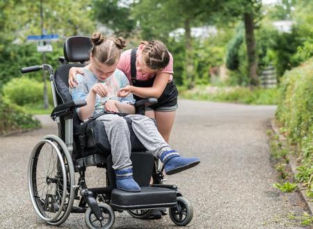 Una niña ayudando a su hermana discapacitada en silla de ruedas