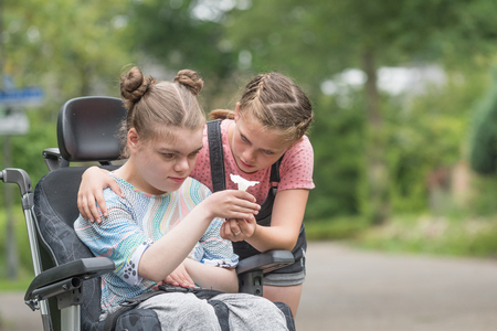 A young girl helping her disabled sister in a wheelchair