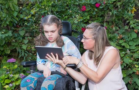 Un niño discapacitado en silla de ruedas cuidado por un trabajador de cuidados voluntario.