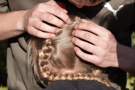Checking a young girls hair for head lice